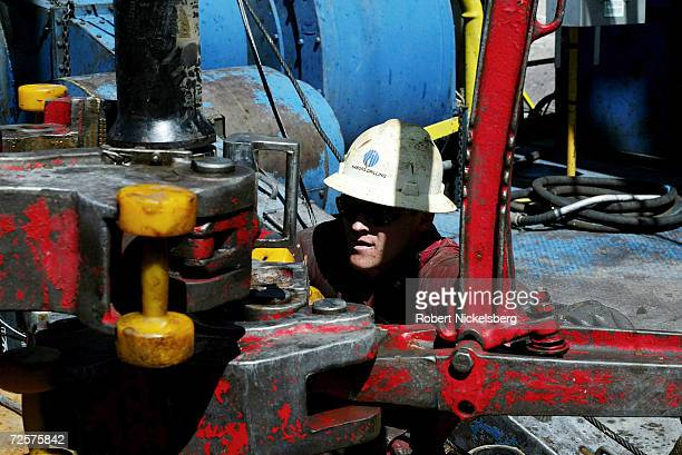 On the floor of a natural gas drilling rig a roughneck tightens a section of new drilling pipe May 8 2004 eight miles north of Evanston Wyoming The...