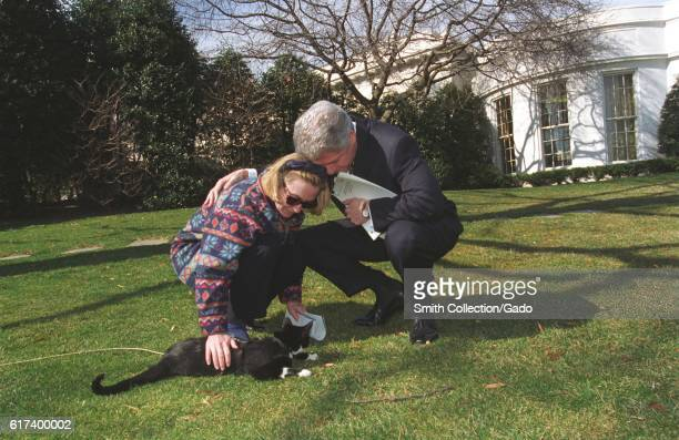 On the front lawn of the White House President Bill Clinton wearing black suit and holding paper bends down beside First Lady Hillary Clinton wearing...