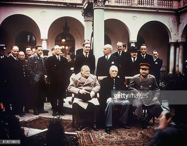 On the grounds of Livadio Palace during the Yalta Conference Soviet Premier Stalin is seated with Winston Churchill and President Roosevelt Standing...