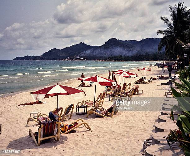On the island of Ko Samui in Southern Thailand tourists relax under beach umbrellas on Chaweng Beach and admire the pristine white sands palm trees...
