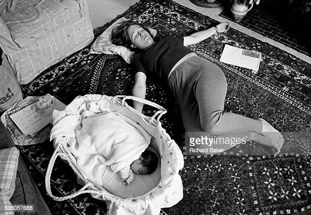 On the living room floor at home a young mother grabs a few minutes to herself to exercises her pelvic floor muscles three weeks after giving birth...