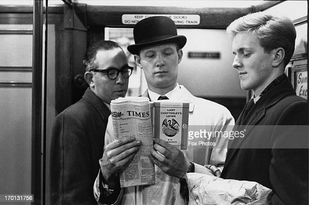 On the London Underground a commuter reads a copy of D H Lawrence's 'Lady Chatterley's Lover' unaware of the fellow passengers surreptitiously...