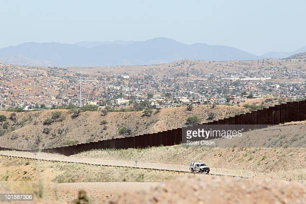 On the outskirts of town a US US Customs and Border Protection agent drives along a fence which separates the cities of Nogales Arizona and Nogales...