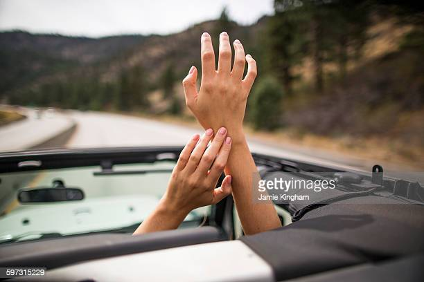 On the road view of young womans hands raised through jeep sunroof