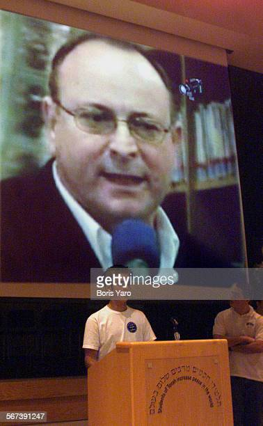 On the screen is former Tel Aviv Mayor Roni Milo answering a question by teleconferencing screen from Israel to Los Angeles to Zack Ulman a student...