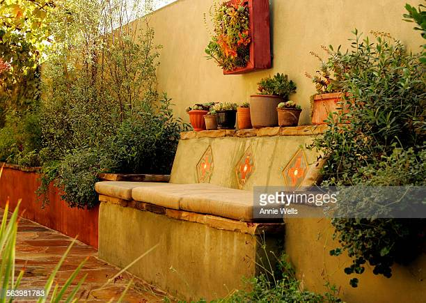 On the side of the house a living area has been created with stucco benches that are accented with fabric pillows and succulents in varieties of pots...