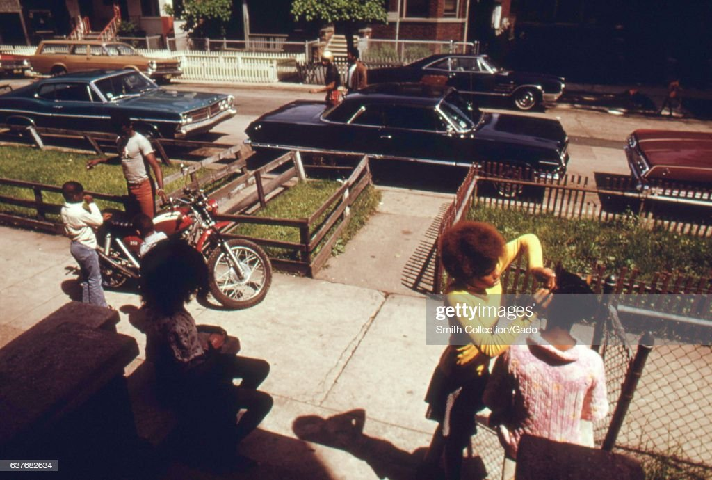 On the sidewalk lined with cars and pedestrians, this West Side neighborhood spends the afternoon outside, including a young woman combing her female friend's Afro while a father shows his young son his red motorcycle and a young girl watches from the shade of the steps, Chicago, Illinois, 1973. Image courtesy National Archives. (Photo via Smith Collection/Gado/Getty Images).