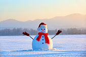 On the white fluffy textured snow alone snowman the friend is standing in nice hat and scarf with red nose. Beautiful winter background.