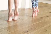 Two bare feet on tippy toes on a wooden floor trying to reach the counter.