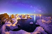 On winter nights, snow and ice cover the rocks by the sea, Beautiful milky way