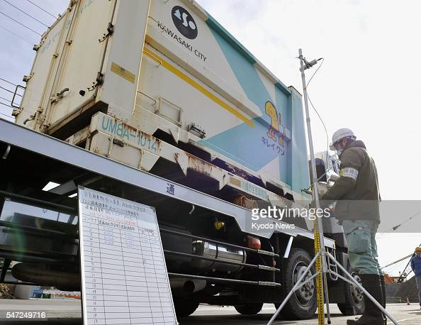 Onagawa Japan A worker measures radiation levels in a container holding debris from the March quake and tsunami before the first batch of rubble is...
