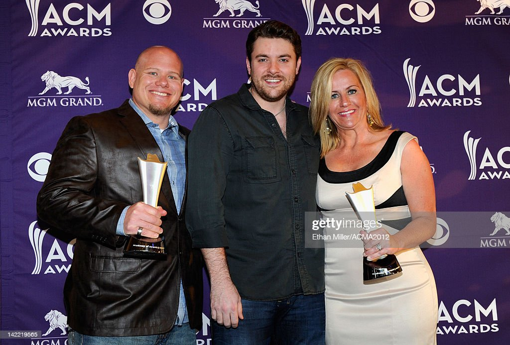 On-Air Personality of the Year for Major Market Winners KYGO-FM Mark 'Rider' Newman (L) and Kelly Ford accept award from Singer Chris Young (C) onstage during ACM Radio Awards Reception at the MGM Grand Hotel/Casino on March 31, 2012 in Las Vegas, Nevada.