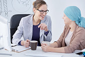 Young oncologist talking to her patient in her office