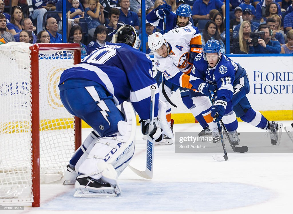 Ondrej Palat #18 of the Tampa Bay Lightning battles for the puck next to goalie <a gi-track='captionPersonalityLinkClicked' href=/galleries/search?phrase=Ben+Bishop&family=editorial&specificpeople=700137 ng-click='$event.stopPropagation()'>Ben Bishop</a> #30 and against <a gi-track='captionPersonalityLinkClicked' href=/galleries/search?phrase=Kyle+Okposo&family=editorial&specificpeople=540469 ng-click='$event.stopPropagation()'>Kyle Okposo</a> #21 of the New York Islanders during the second period of Game Two of the Eastern Conference Second Round in the 2016 NHL Stanley Cup Playoffs at the Amalie Arena on April 30, 2016 in Tampa, Florida.