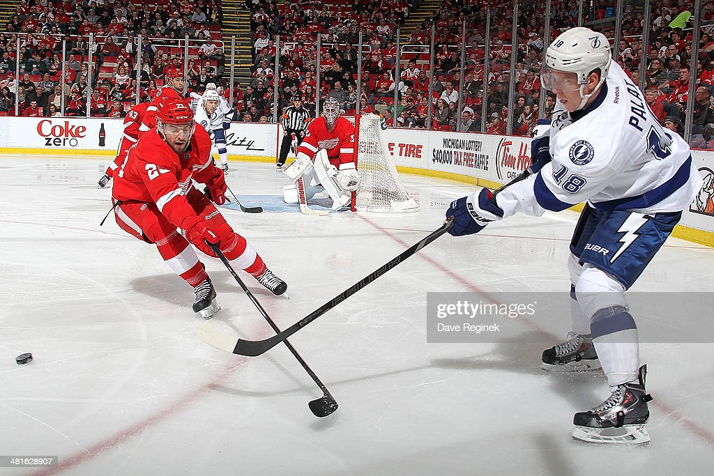Ondrej Palat #18 of the Tampa Bay Lightning passes the puck as <a gi-track='captionPersonalityLinkClicked' href=/galleries/search?phrase=Brian+Lashoff&family=editorial&specificpeople=5529056 ng-click='$event.stopPropagation()'>Brian Lashoff</a> #23 of the Detroit Red Wings defends him during an NHL game on March 30, 2014 at Joe Louis Arena in Detroit, Michigan. Detroit defeated Tampa Bay 3-2