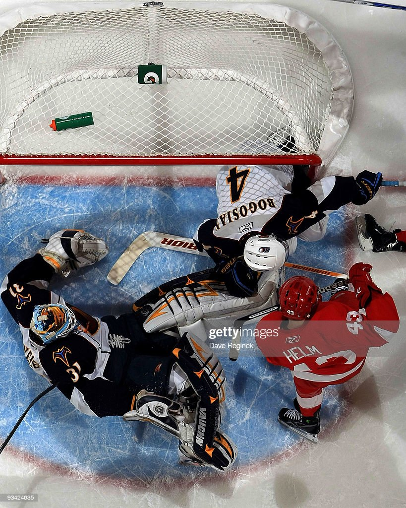 Ondrej Pavelec #31 of the Atlanta Thrashers makes a save as teammate Zach Bogosian #4 clears the net and Darren Helm #43 of the Detroit Red Wings looks for the rebound during a NHL game at Joe Louis Arena on November 25, 2009 in Detroit, Michigan. Atlanta defeated Detroit 2-0.