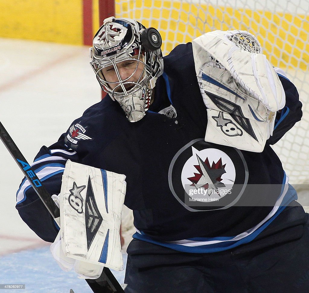 Ondrej Pavelec #31 of the Winnipeg Jets blocks a shot on goal in third-period action in an NHL game against the Vancouver Canucks at the MTS Centre on March 12, 2014 in Winnipeg, Manitoba, Canada.