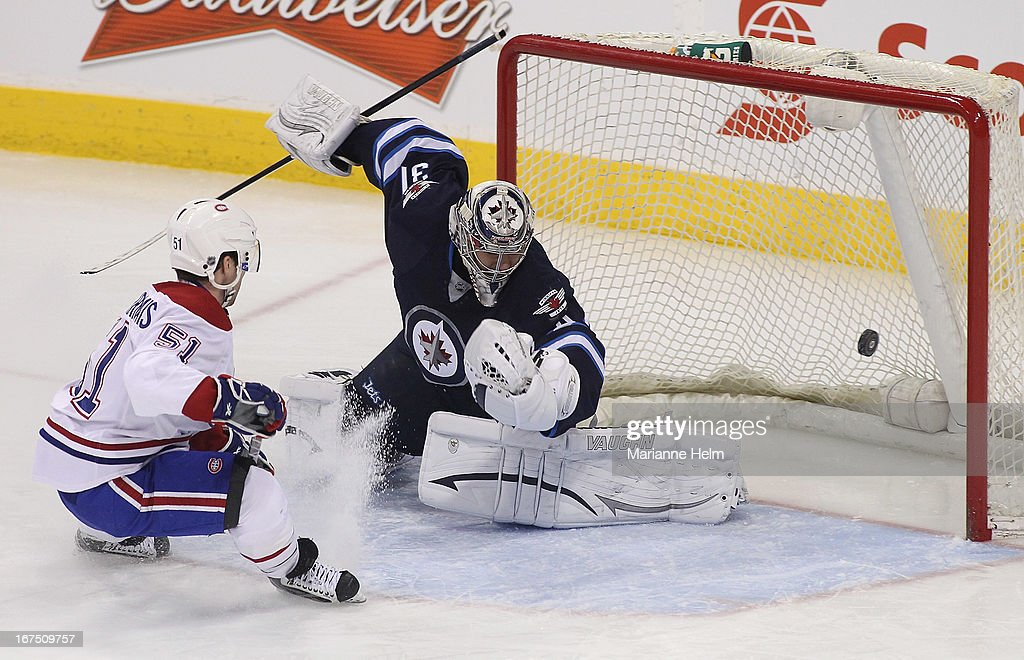 Ondrej Pavelec of the Winnipeg Jets blocks shot on goal by David Desharnais of the Montreal Canadiens during first period NHL action on April 25 2013...