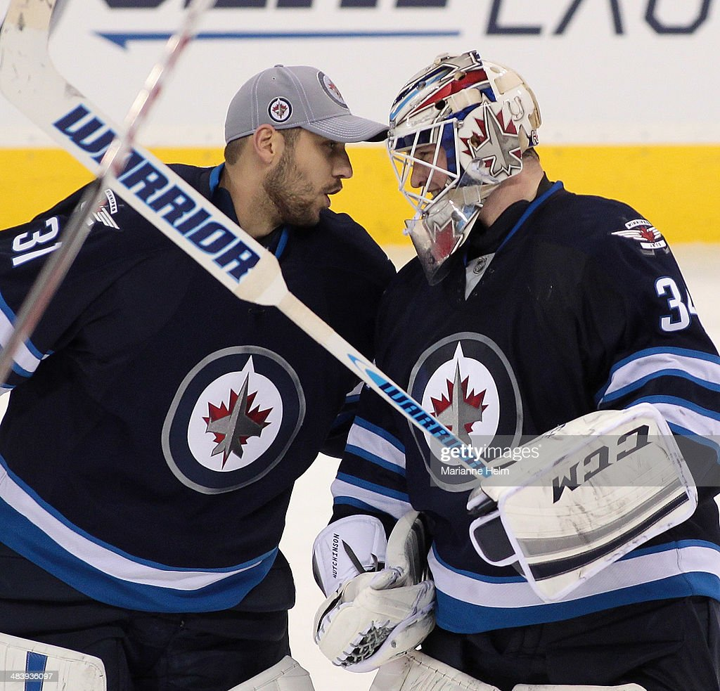 Ondrej Pavelec #31 of the Winnipeg Jets congratulates Michael Hutchinson #34 for his first NHL win after shootout action in an NHL game against the Boston Bruins at the MTS Centre on April 10, 2014 in Winnipeg, Manitoba, Canada.