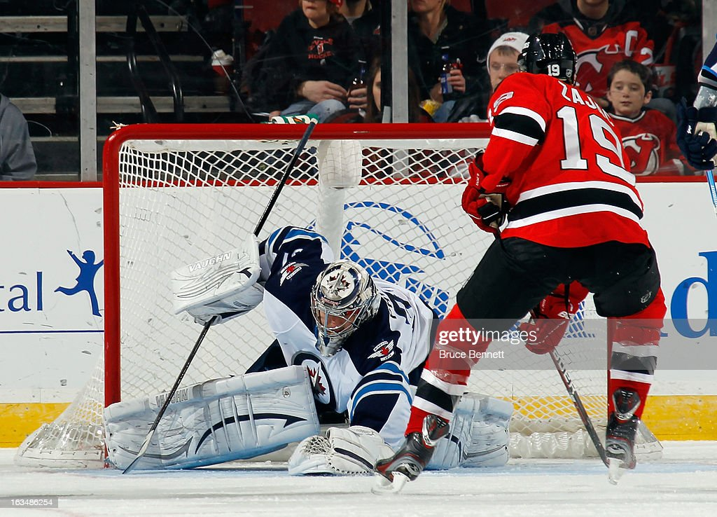 Ondrej Pavelec #31 of the Winnipeg Jets covers the puck as Travis Zajac #19 of the New Jersey Devils looks for a rebound at the Prudential Center on March 10, 2013 in Newark, New Jersey.The Devils defeated the Jets 3-2 in the shootout.