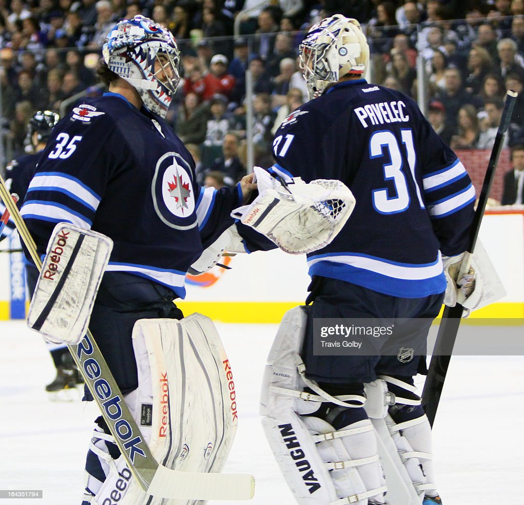 Ondrej Pavelec #31 of the Winnipeg Jets gets a fist bump from teammate <a gi-track='captionPersonalityLinkClicked' href=/galleries/search?phrase=Al+Montoya&family=editorial&specificpeople=213916 ng-click='$event.stopPropagation()'>Al Montoya</a> #35 after being pulled during second-period action against the Washington Capitals at the MTS Centre on March 22, 2013 in Winnipeg, Manitoba, Canada.