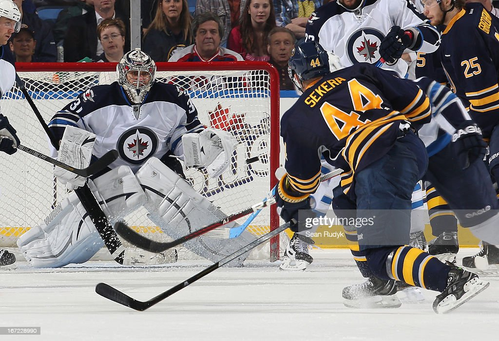 Ondrej Pavelec #31 of the Winnipeg Jets keeps a close eye one the puck as Andrej Sekera #44 of the Buffalo Sabres fires a third period shot at First Niagara Center on April 22, 2013 in Buffalo, New York.