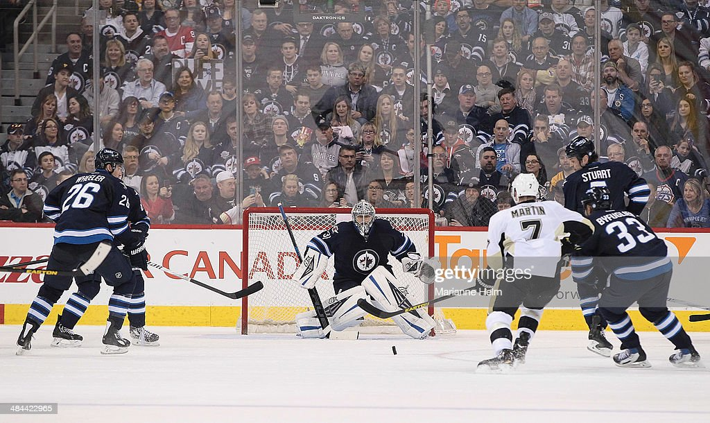 Ondrej Pavelec #31 of the Winnipeg Jets keeps his eyes on the puck during second period action of an NHL game against the Pittsburgh Penguins at the MTS Centre on April 3, 2014 in Winnipeg, Manitoba, Canada.