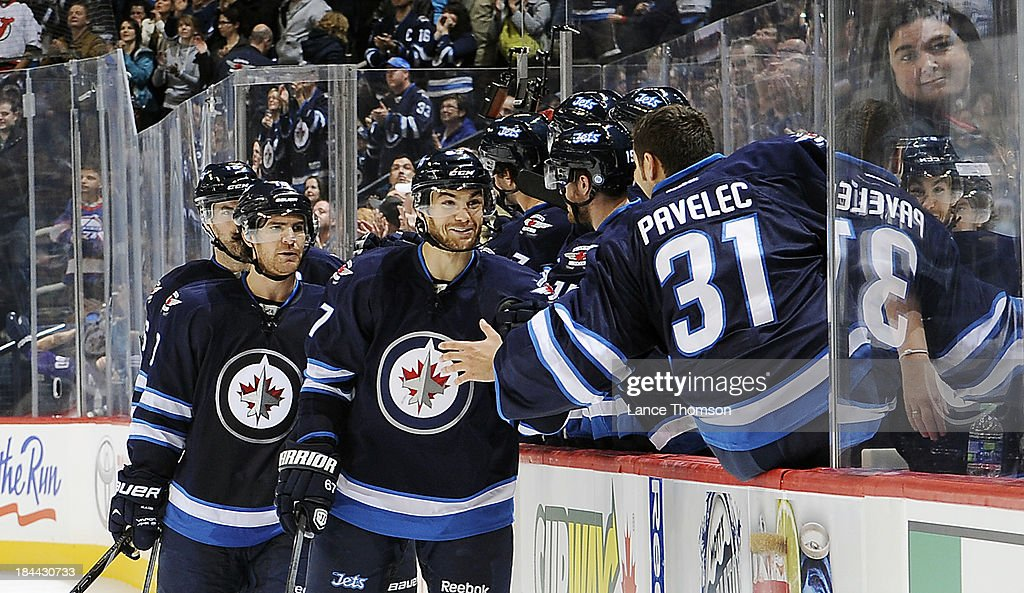 Ondrej Pavelec #31 of the Winnipeg Jets leans over the bench to celebrate with teammate <a gi-track='captionPersonalityLinkClicked' href=/galleries/search?phrase=Michael+Frolik&family=editorial&specificpeople=537965 ng-click='$event.stopPropagation()'>Michael Frolik</a> #67 after an insurance goal late in the third period over the New Jersey Devils at the MTS Centre on October 13, 2013 in Winnipeg, Manitoba, Canada. The Jets defeated the Devils 3-0.