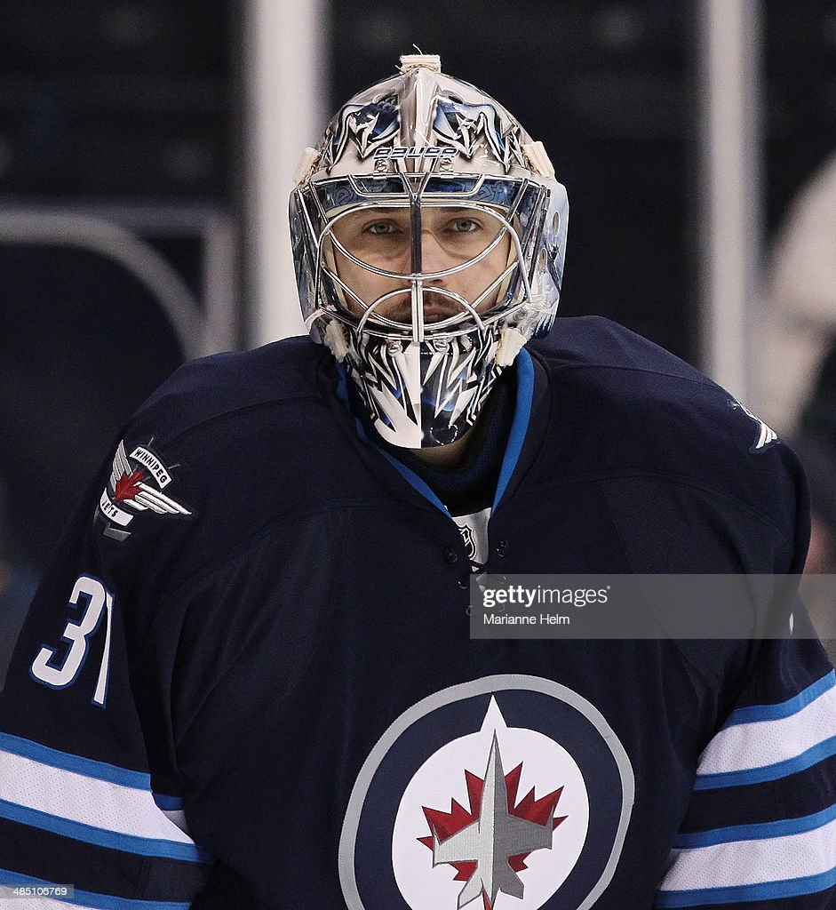 Ondrej Pavelec #31 of the Winnipeg Jets looks down the ice during warmup before an NHL game against the Boston Bruins at the MTS Centre on April 10, 2014 in Winnipeg, Manitoba, Canada.
