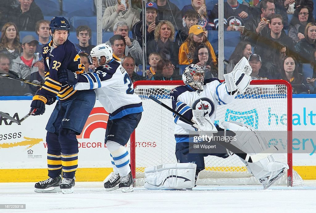 Ondrej Pavelec #31 of the Winnipeg Jets makes a glove save while teammate Grant Clitsome #24 shoves John Scott #32 of the Buffalo Sabres out of the way on April 22, 2013 at the First Niagara Center in Buffalo, New York.