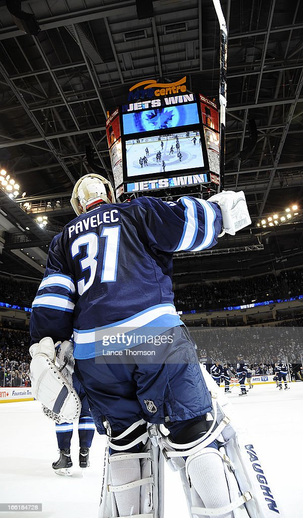 Ondrej Pavelec #31 of the Winnipeg Jets raises his stick in victory after backstopping the Jets to a 4-1 win over the Buffalo Sabres at the MTS Centre on April 9, 2013 in Winnipeg, Manitoba, Canada.