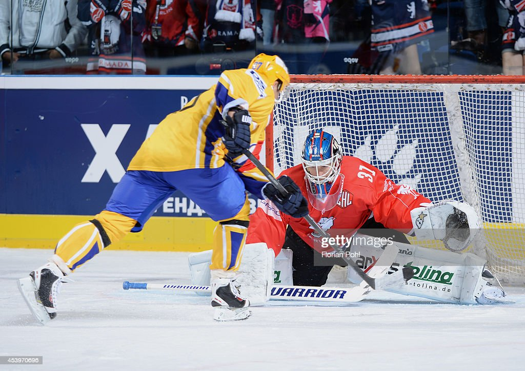 Ondrej Vesely #87 of PSG Zlin attempts to score against Petri Vehanen #31 of Eisbären Berlin during the Champions Hockey League group stage game between Eisbaeren Berlin and HC Zlin on August 22, 2014 in Berlin, Germany.