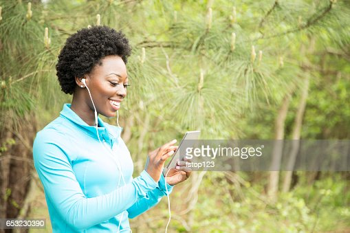 One African descent woman exercising, using cell phone in neighborhood park. : Stock Photo