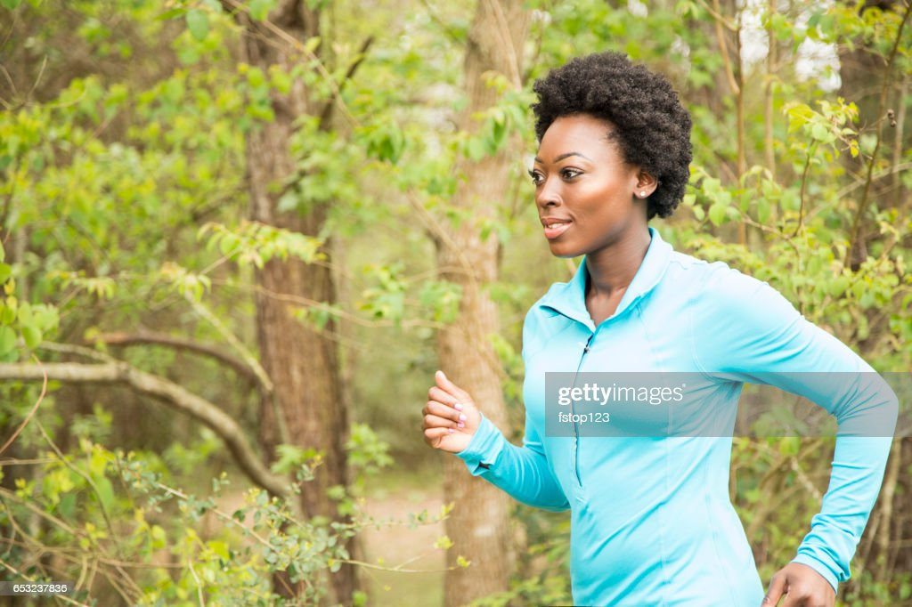 One African descent woman running in neighborhood park. : Stock-Foto