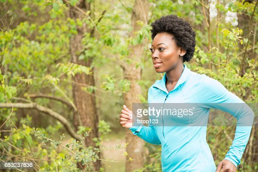 One African descent woman running in neighborhood park. : Bildbanksbilder