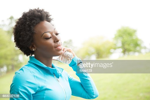 One African descent woman takes water break in neighborhood park. : Stock Photo