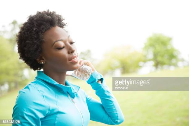 One African descent woman takes water break in neighborhood park.