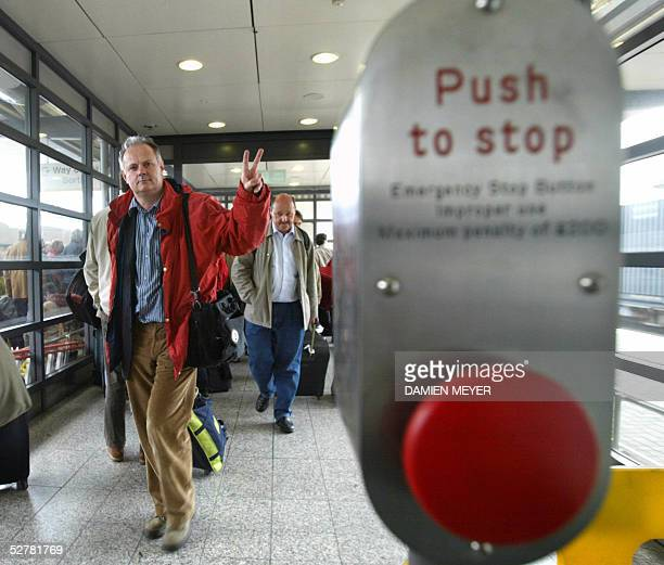 One among hundreds of French surgeons flashes the V sign as he arrives 10 May 2005 at the Ashford railway station coming from on a Eurostar train at...