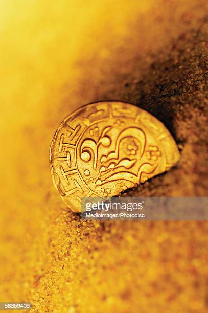 One ancient coin, partially buried in sand