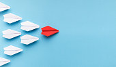 New trends concept. One red paper plane followed by group of white ones on blue background, copy space