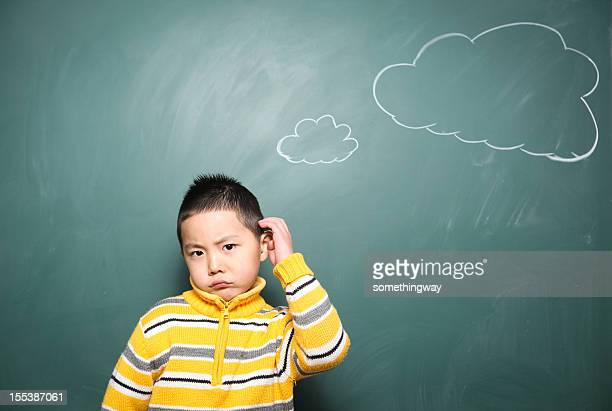 one boy is thinking questions in front of the blackboard