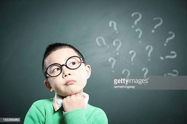Un petit garçon se tient devant le tableau noir penser