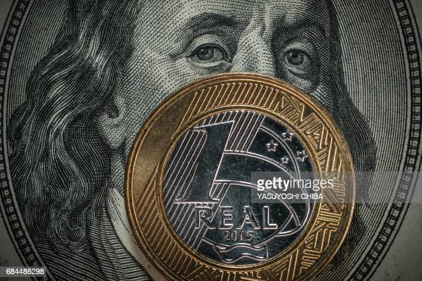 A one Brazilian real coin is backdropped against a 100 US dollar bill in Rio de Janeiro Brazil on May 18 2017 Brazilian financial markets plummeted...