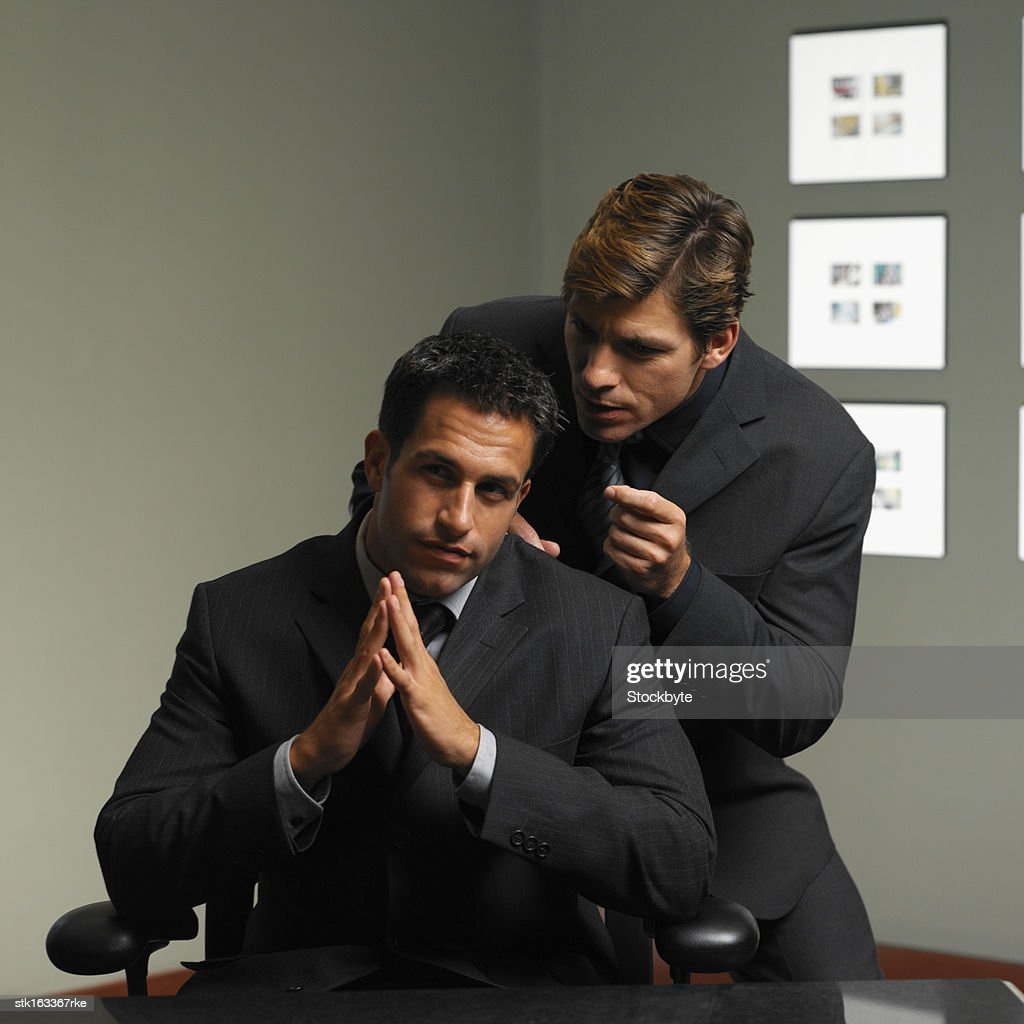 one businessman leaning over another businessman whispering in his ear portrait : Stock Photo