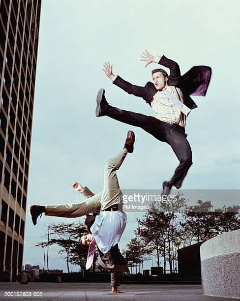 One businessman leaping, one doing one arm handstand, low angle view