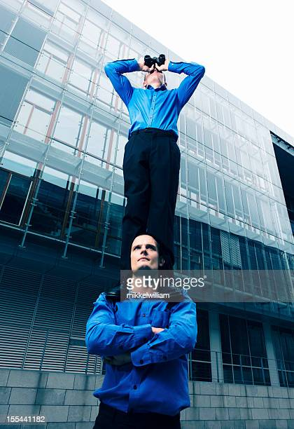 One businessman with binoculars stands on the shoulder of coworker