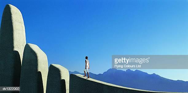One Businesswoman Walking towards Rock formation on Mountain Top
