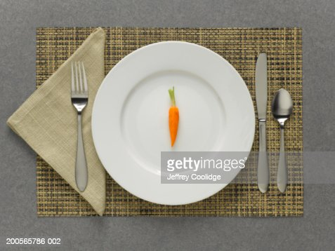 One carrot on plate with table setting, elevated view : Stock Photo
