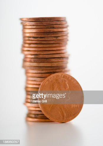 One cent coin in front of stack of pennies