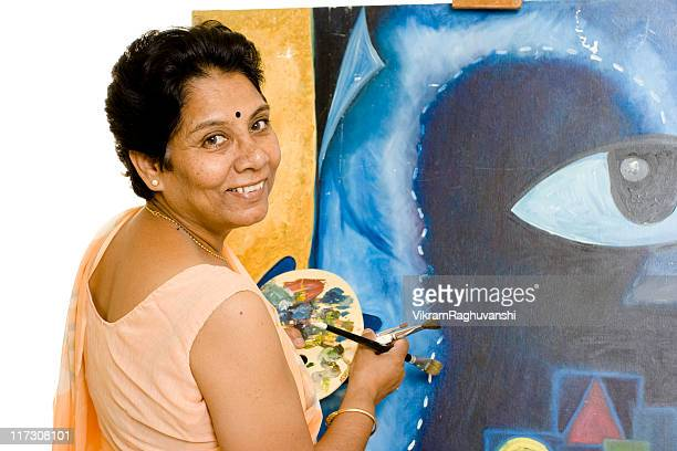 One Cheerful Indian Senior Woman Artist Working on her Painting